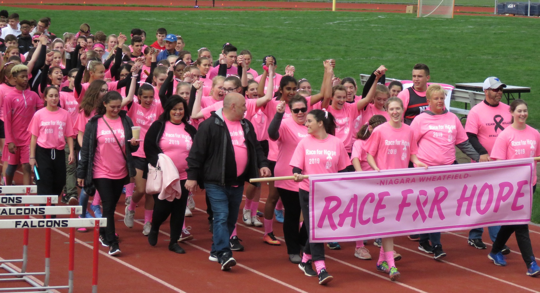 During an honorary lap, the Niagara-Wheatfield track and field team crosses the finish line alongside cancer survivors and fighters at a `Race for Hope.` (Photos by David Yarger)