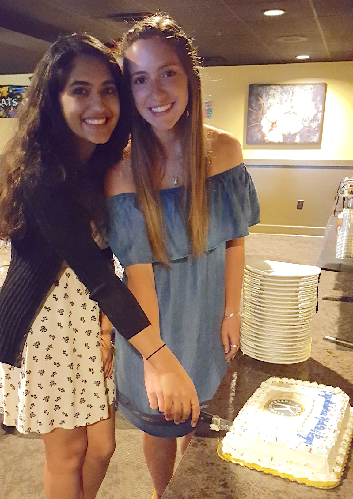 Scholarship recipients Madison Klondonas and Perya Bhagchandani cut their cake at a scholarship dinner at Jack's Backyard Grill.