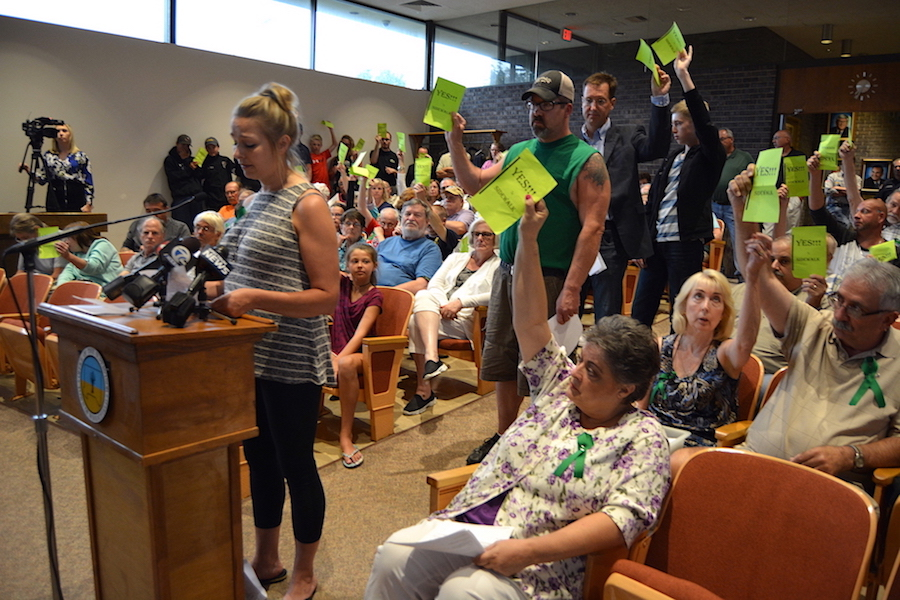 Residents hold up signs encouraging a `Yes` vote, while Kelly Dueger urges Wheatfield Town Board members to vote in favor of installing a sidewalk on Krueger Road.