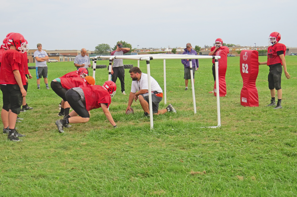 Niagara-Wheatfield High School football coach Russell Nixon works with his linemen.