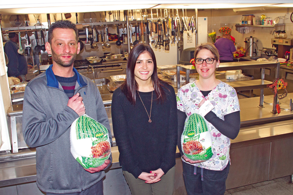 Francesca Catanese, center, events and volunteer manager at Community Missions of Niagara Frontier Inc., accepts a donation of two turkeys from Dr. Nicholas Ryan and Jen Paonessa of Notaro Chiropractic. Ryan and Paonessa delivered the turkeys Monday to Community Kitchen on Buffalo Avenue in Niagara Falls. (Photo by Larry Austin)