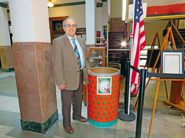 North Tonawanda Mayor Arthur Pappas poses with the Rockin' With Santa donation barrel at North Tonawanda City Hall.