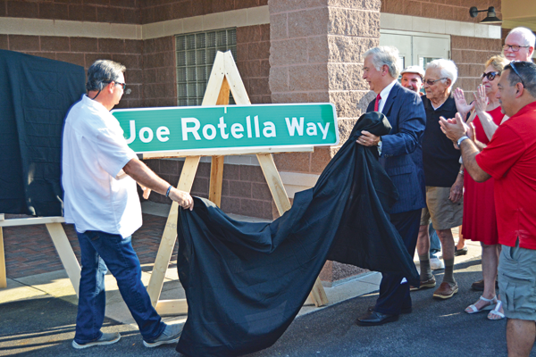 Town of Niagara Supervisor Lee Wallace (left) and Rick Rotella (right) unveil the Joe Rotella Way street sign at Monday night's ceremony.