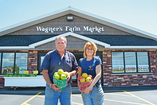 Wagner's Farm Market and Grill owners Peter Wagner and Amy Wagner Winkelmann display some of their homegrown apples in front of the store's new façade.