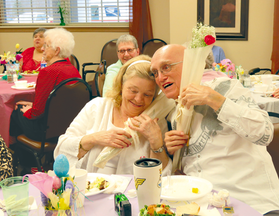 Carl and Liz Blessing, the lone couple, are pictured with their flowers at the 10th anniversary event Tuesday. Also, an anniversary cake was baked to honor the facility's special day. (Photos by David Yarger)