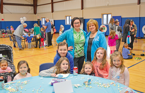 Debbie Reed (standing, at right) and Olivia Toner smile for a photo with younger visitors at one of the children's activity stations at last year's Wheatfield Winterfest. (File photo by Lauren Zaepfel)
