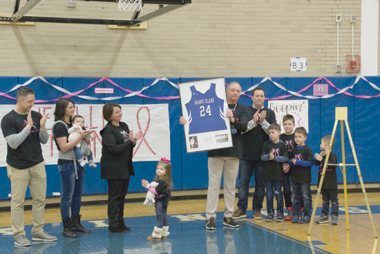 Grand Island Central School Athletic Director Jon Roth holds his daughter Julie Neville's No. 24 jersey that was retired in a ceremony Friday.