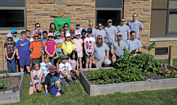 Students at Kaegebein Elementary School are pictured with volunteers, including those from Thermo Fisher Scientific, who helped establish the school's courtyard garden. (Photo by Larry Austin)