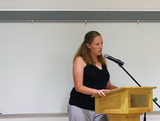 Kate Girard speaks at Wednesday's Board of Education meeting about the hiring process of a new Huth Road Elementary principal. Looking on at left is Max Pikula, who was appointed to the job moments later. (Photo by Larry Austin)