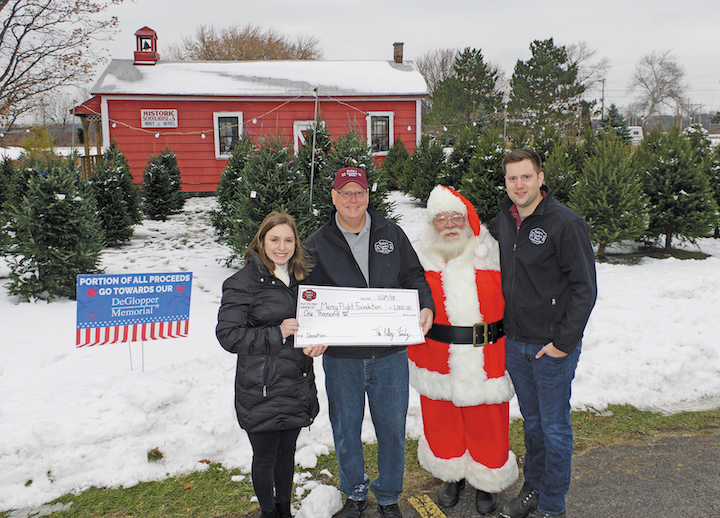 Kelly's Country Store, 3121 Grand Island Blvd., presented a $1,000 donation to Mercy Flight on Thursday. The money was raised from proceeds of last year's Christmas tree sales. Pictured at the presentation are, from left: Jessica McKay, marketing and development coordinator for Mercy Flight; Kevin Kelly, vice president of Kelly's Country Store, Santa Claus, and Adam Kelly, assistant manager at Kelly's Country Store. (Photo by Larry Austin)