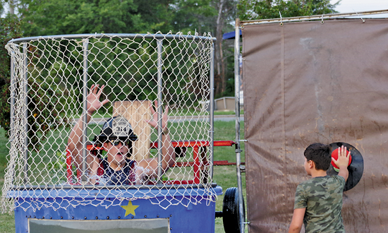 Grand Island firefighter Dakota Bower falls into the water during a fundraiser at National Night Out Tuesday. Money raised from the dunk tank went to the Grand Island Neighbors Foundation. (Photo by Larry Austin)