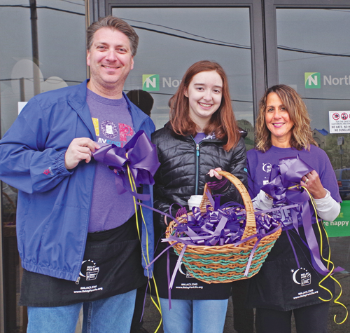 Mark Gorton, Sara Gorton and Lisa Dudley sell purple ribbons and bows at the 2018 Paint the Town Purple event.