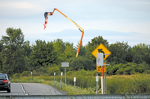 A crane with an American flag rises above the property where an Amazon e-commerce warehouse is proposed for development on Long Road. The height of the flag approximates the height of the proposed warehouse, 87 feet. (Photo by Larry Austin)