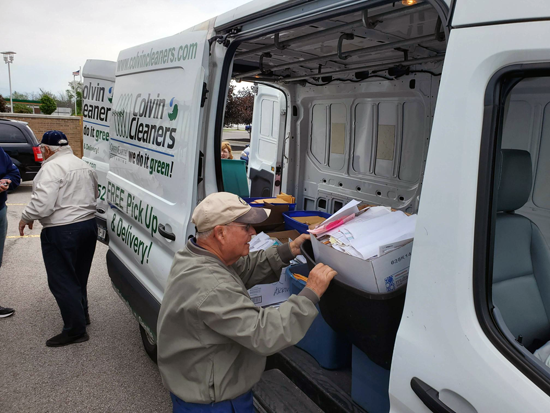 Grand Island Rotary member Dr. Jerry Barlow unloads a large donation to be shredded.