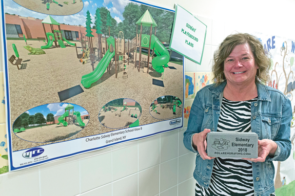 Linda Samland, chair of the Sidway Playground Committee, holds a sample engraved brick on sale to raise funds for a new playground at the school. (Photo by Larry Austin)