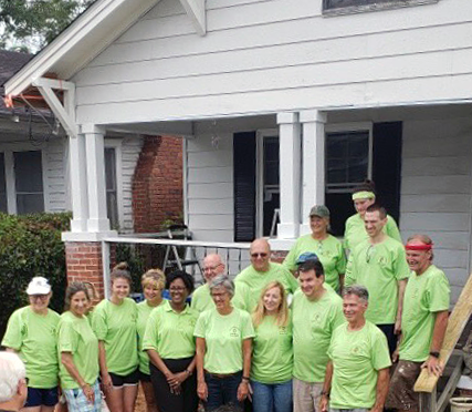A work crew with the United Methodist Bishop and District Superintendent are pictured in glowworm green work clothes during a mission trip in July.