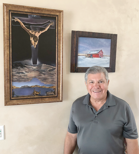 Thomas Insana with two of his paintings set for display at the Grand Island Memorial Library.