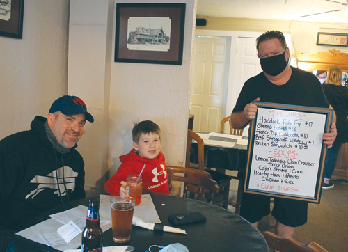Mike Carr, right, owner of the Village Inn at 1488 Ferry Road, shows the daily specials menu to longtime customer Marty Rastelli, left, and his son, Cooper, 6. They were among the first customers to dine indoors at the restaurant on the day after a Jan. 14 court ruling allowing restaurant owners in Erie County to reopen for indoor dining under `yellow zone` COVID-19 restrictions. (Photo by Karen Carr Keefe)