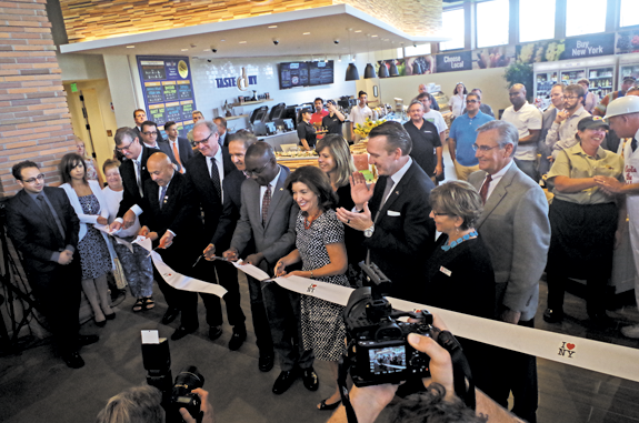 Cutting the ceremonial ribbon inside the new Western New York Welcome Center on Alvin Road are, from left, Niagara Falls Mayor Paul Dyster, Assemblyman Angelo Morinello, Empire State Development CEO Howard Zemsky, U.S. Rep. Brian Higgins, Buffalo Mayor Byron Brown and Lt. Gov. Kathy Hochul. Looking on is Town of Grand Island Supervisor Nathan McMurray. The center includes a Taste NY café. Below, right, McKenna Prochaska of Grand Island served some of the Taste NY items during the ribbon-cutting event. (Photos by Larry Austin)