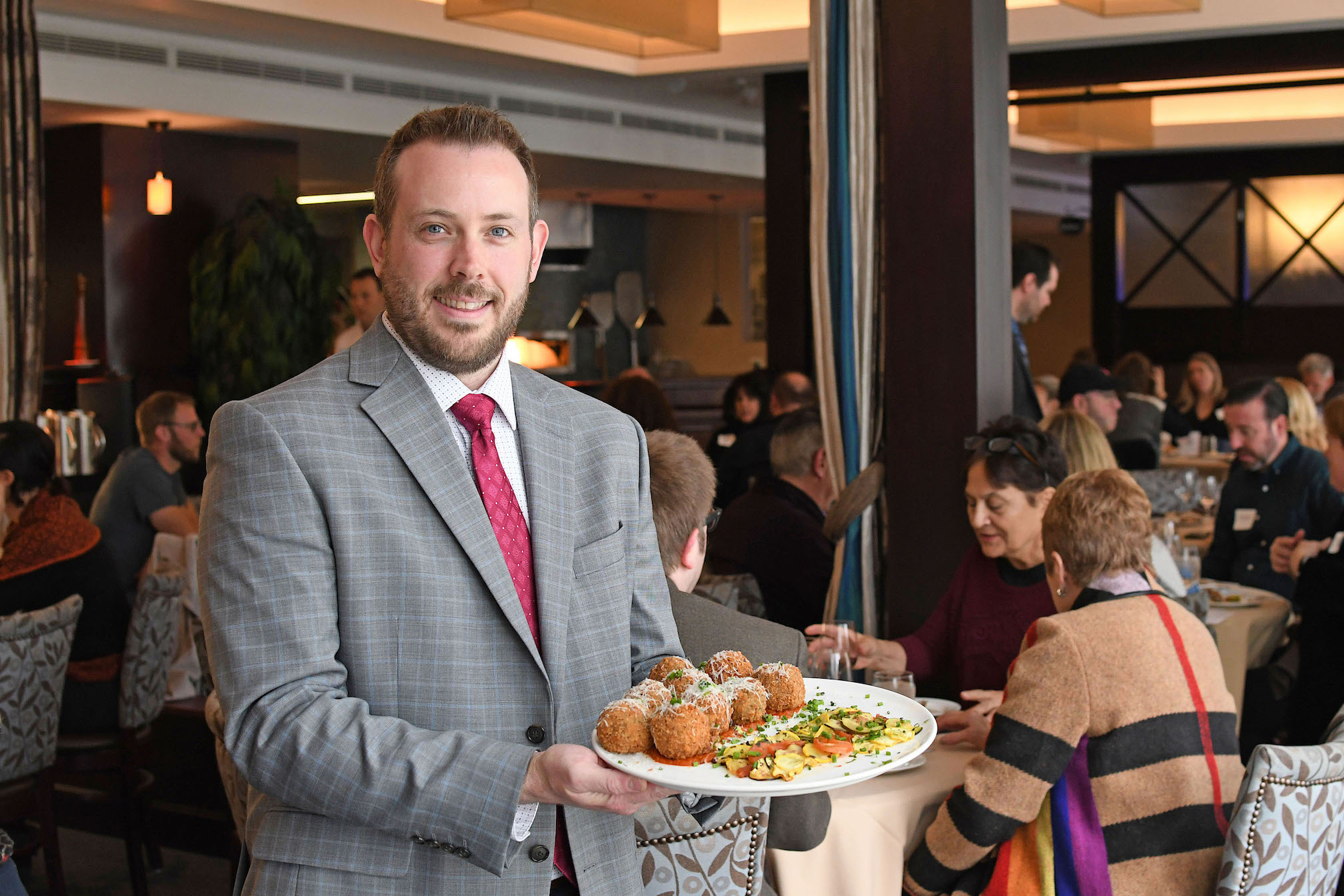 The Niagara Falls Culinary Institute hospitality instructor Daniel DiPirro presents a plate of arancini featured on the seasonal menu at Savor Restaurant.