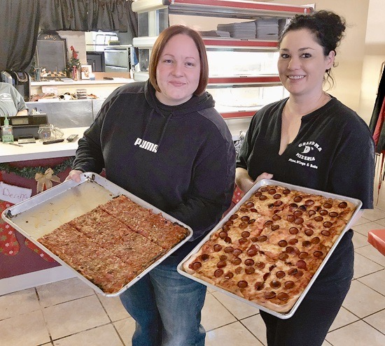 Deana Barlow and Jamah show off some of the pizza options at `The Original Destino's.`