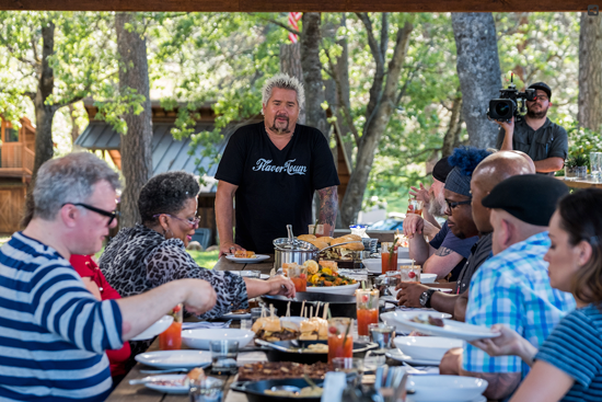 Guy Fieri looks over the work created by contestants on `Guy's Big Project.`
