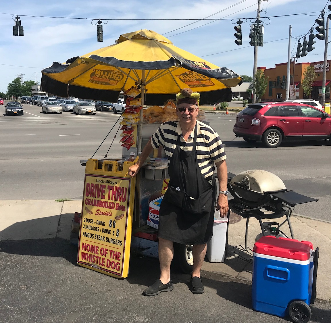 Mike Heigel, in his famous hot dog cap, stands by Uncle Mikey's Drive Thru hot dog stand at the corner of Military Road and Niagara Falls Boulevard. (Photo by David Yarger)