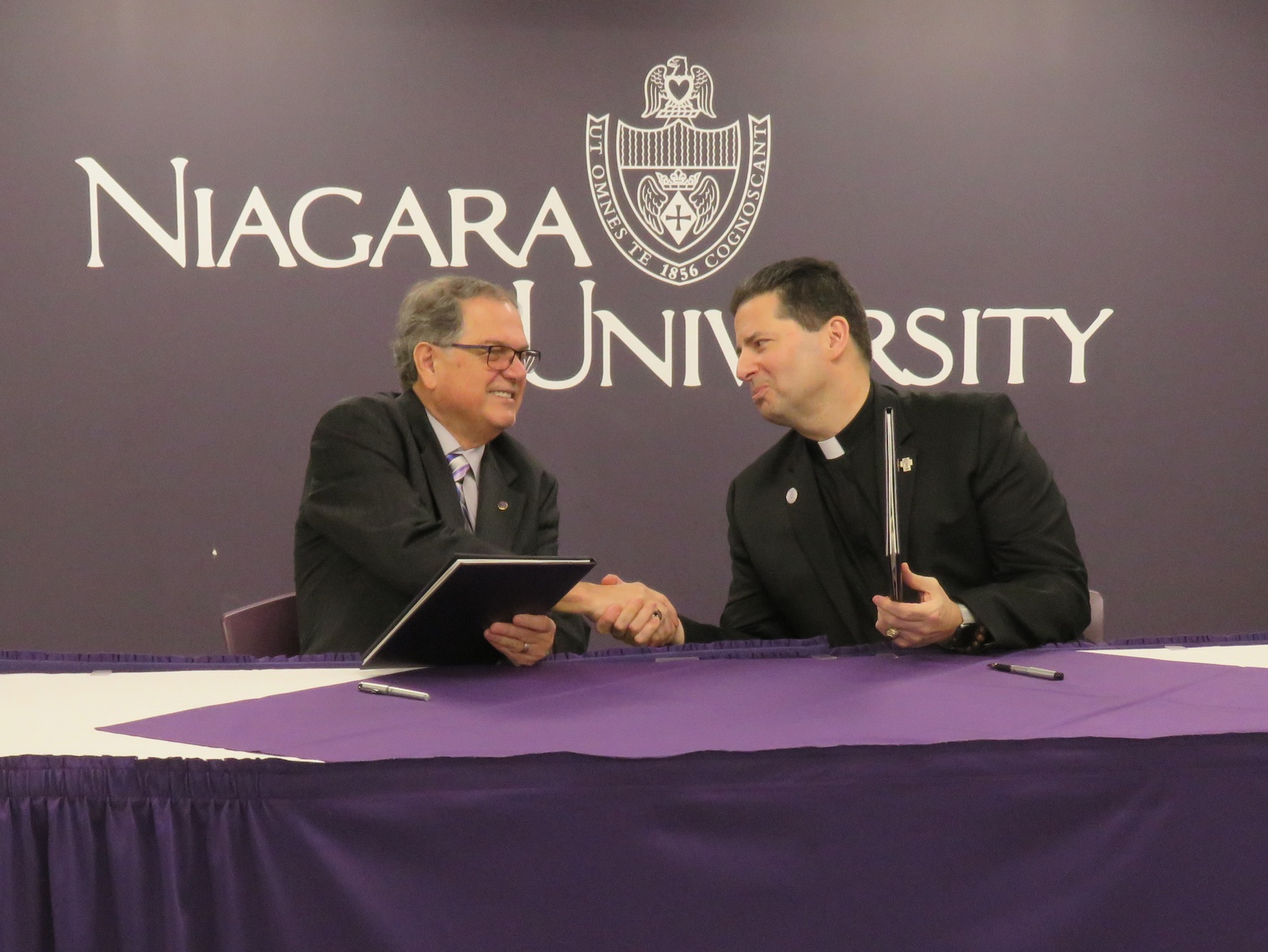 From left, Niagara County Community College President Dr. William Murabito and Niagara University President Rev. James J. Maher C.M. shake hands following a memorandum of understanding. (Photo by David Yarger)