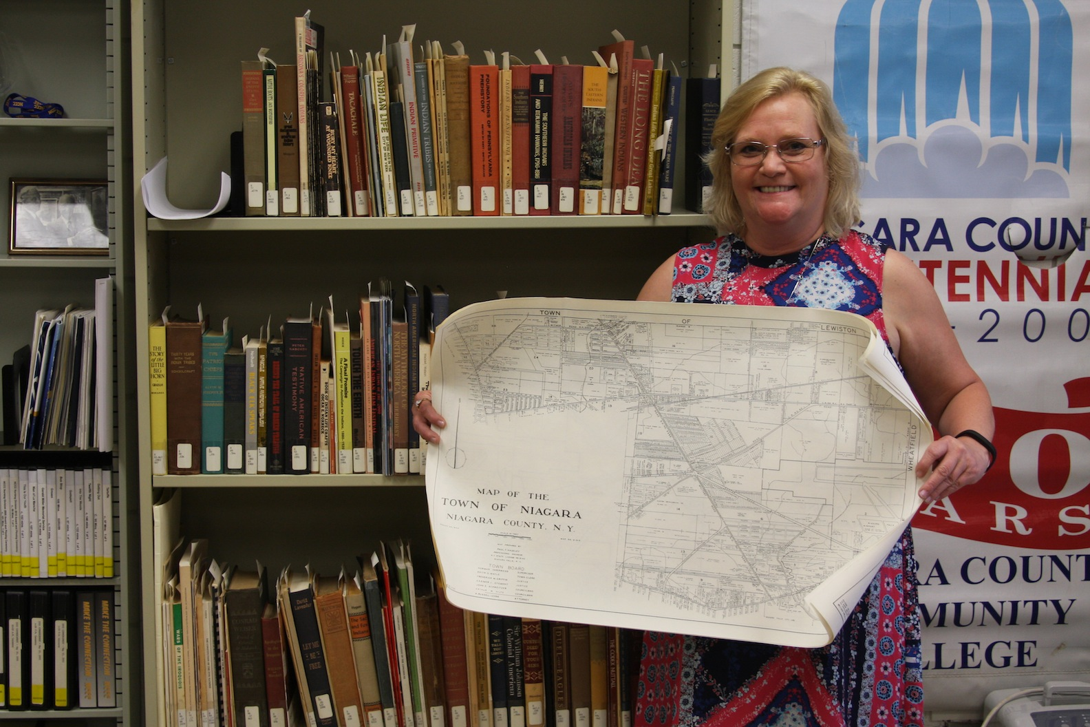NCCC Library employee, Barbara Rupple pictured with a map of the Town of Niagara.
