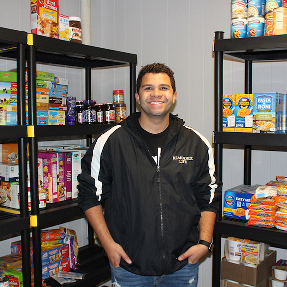 Freddie Wade, a community adviser in residence life, stands in the new student food pantry at Niagara University.