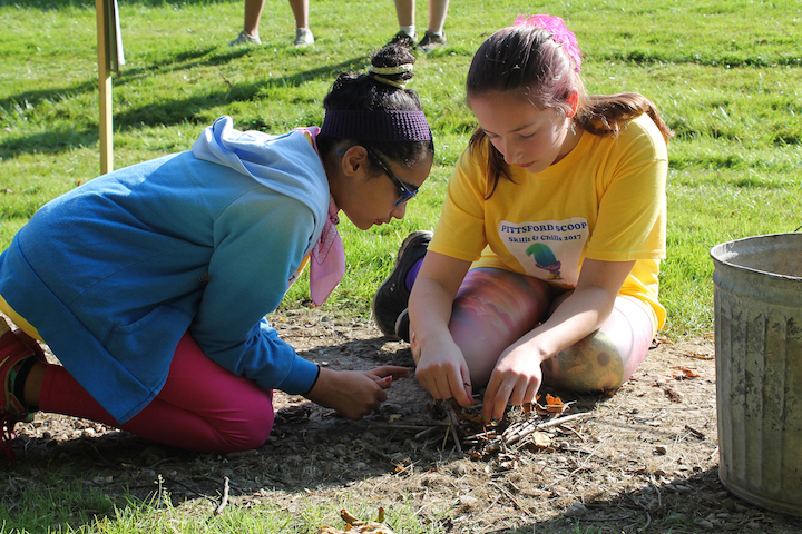 Girls from Pittsford Trolls Team 4444 work on fire-building.