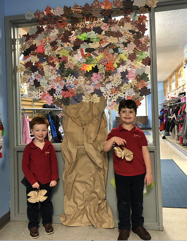 Brendan Burns and Armen Hurtgam stand with ornaments they made in front of the giving tree created by pre-K 3 and pre-K 4 students at St. Peter's R.C. School. The students sold `leaves` for the tree for $1 and raised $240 for Niagara Hospice. The ornaments will be displayed on the Niagara Hospice Christmas tree at the New York Power Authority Festival of Trees.