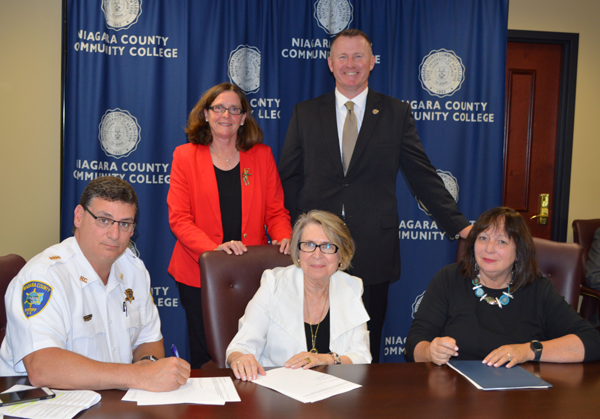 Pictured, from left, seated: Niagara County Sheriff James Voutour, Niagara County Community College Officer in Charge Dr. Luba Chliwniak and YWCA of the Niagara Frontier CEO Kathleen Granchelli; and standing: YWCA of the Niagara Frontier Vice Present of Programs Mary Brennan-Taylor and New York State Police Campus Sexual Assault Victims Unit Senior Investigator Thomas Gibbons.