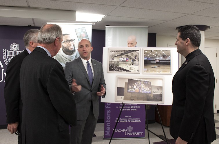 Simon Gray, Niagara University's director of athletics, discusses the forthcoming installation of new high-definition LED video boards in the university's athletic arenas with Dr. Tim Ireland, provost; Brian Crosby, trustee; and the Rev. James J. Maher, C.M., president.