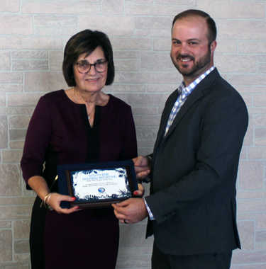 Patti Wrobel, executive director of Niagara University's Rev. Joseph L. Levesque, C.M. Institute for Civic Engagement, accepts the `Project of the Year` award on behalf of the south end housing initiative for its signature `Rock the Block` event, from Niagara Beautification Commission's chairman, Tom Lowe.