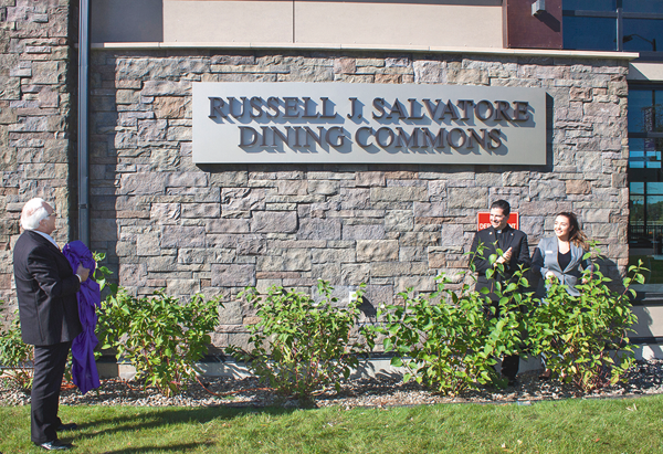 Local restaurateur and philanthropist Russell J. Salvatore, the Rev. James J. Maher, C.M., president of Niagara University, and NU senior Sophia Castro unveiled a new name for the university's dining commons, which commemorates a gift from Salvatore.