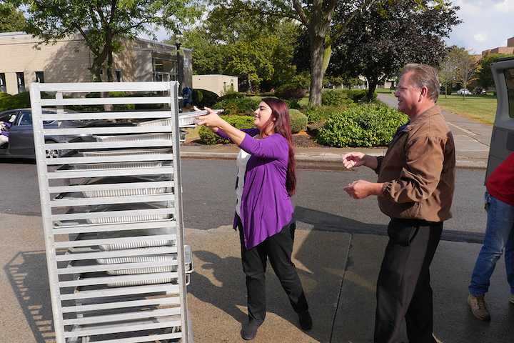 Nicole Slipko, catering manager for the Metz Culinary Management operation at Niagara University, helps Grant Babcock, operations manager of Community Missions of Niagara Frontier, load trays of food that will be given to guests of the service agency and the Heart, Love & Soul food pantry and dining room.