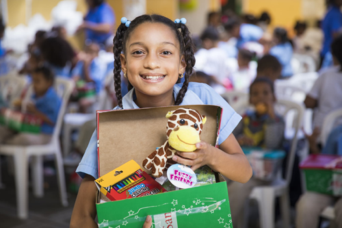 A girl in the Dominican Republic shows off the `wow` toy she received in her shoebox gift. (Photo courtesy of Operation Christmas Child)