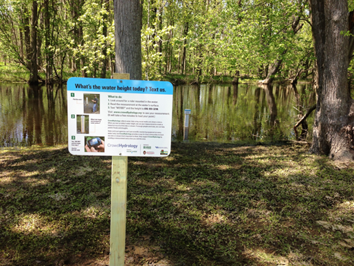 A CrowdHydrology site in Michigan. Stations include a giant measuring staff and a sign explaining how passersby can contribute to the project by texting water levels to scientists. (Photo credit: CrowdHydrology)