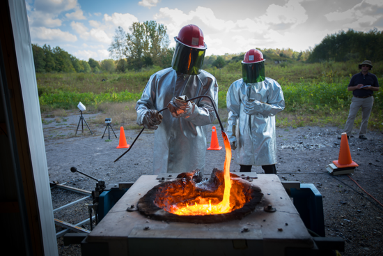 Ingo Sonder, a research scientist at UB's Center for Geohazards Studies, stirs the molten rock as it melts inside the furnace. (Photo credit: Douglas Levere/University at Buffalo)