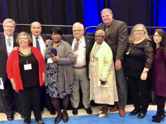Ernestine Gayle receiving award at Cerebral Palsy Associations of New York State conference: (from left) Empower CEO Jeff Paterson, Empower Director of Program Operations/Quality Assurance Administration Diane Baehre, Empower Board President Tom Caserta, Ernestine Gayle, Empower board member Bob DiFrancesco, Jackie Davis, Empower Director of Community Housing William Krayss, Empower Coordinator of Community Support Services Robin Stevens, and Empower Assistant Education Supervisor Amy Scott.