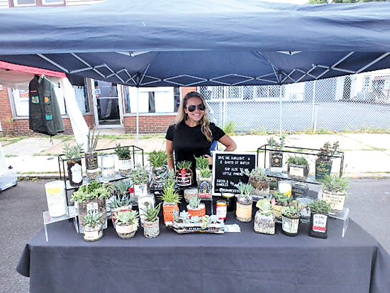 Julia Stephens of Williamsville shows off her liquor bottles reused as succulent planters at Oliver Street Art Festival.