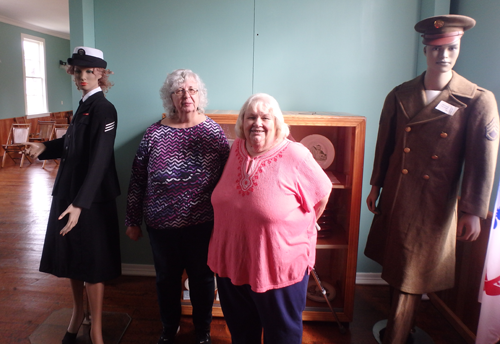 Bonnie Haskell, left, and Pat Thompson stand with mannequins made up like wartime.