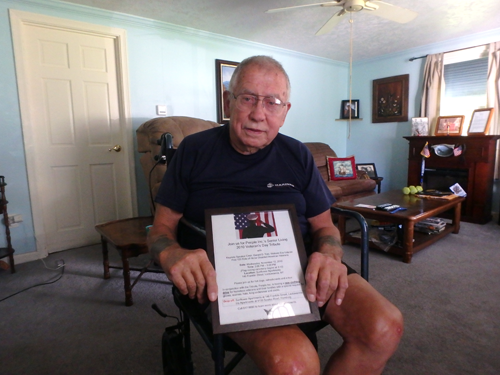 Gerald Tidd in his home holding one of the plaques on his walls commemorating his work for homeless veterans.