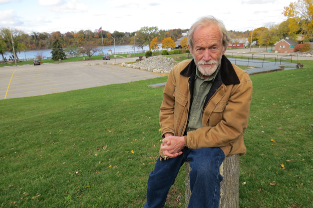 Lance Henriksen sits in front of the Lewiston waterfront.