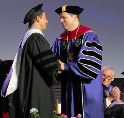 Raine Maida shakes hands with the Rev. James J. Maher, C.M., president of Niagara University.
