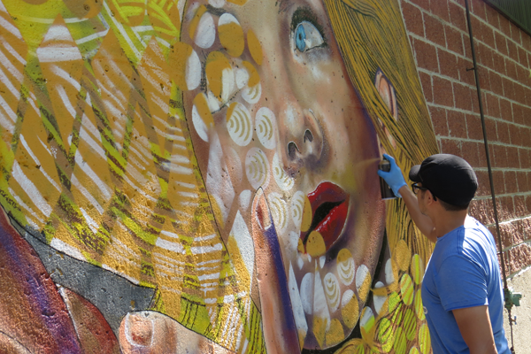 Chuck Tingley works on a permanent mural at Artpark in Lewiston.