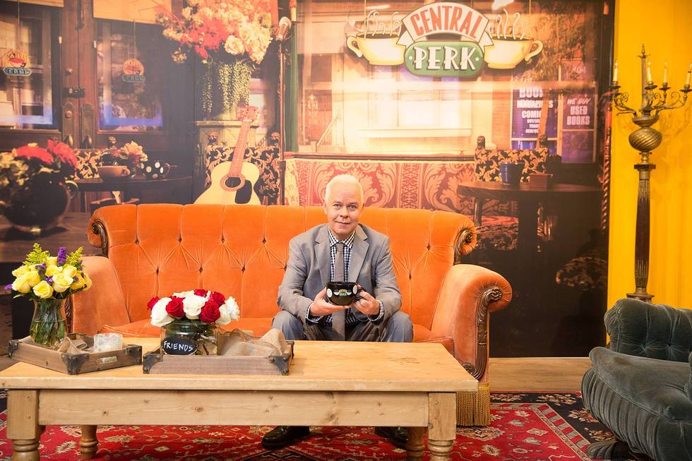 Actor James Michael Tyler, who played the famously deadpan barista Gunther on `Friends,` poses for a picture on the iconic orange couch from the show at the pop-up replica of Central Perk. (photo ©2014 Warner Bros. Entertainment Inc. All rights reserved.)