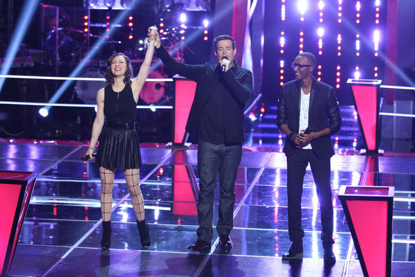 `The Voice`: Host Carson Daly holds Kat Robichaud's arm in victory upon her `Battle` with R. Anthony. (NBC photo by Tyler Golden)