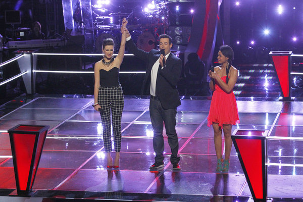 `The Voice` Carson Daly lifts the hand of Audrey Karrasch following her battle with Jamila Thompson. (NBC photo by Trae Patton)